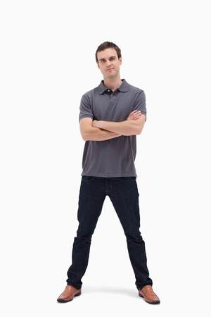 legs apart: Standing man crossing his arms and his legs apart against white background Stock Photo