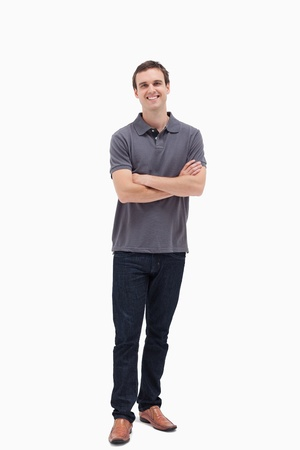 standing man: Standing man smiling while crossing his arms and against white background