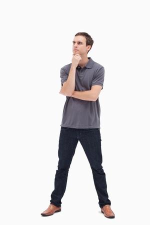 legs apart: Hombre de pie pensativo y las piernas abiertas mirando hacia arriba contra el fondo blanco
