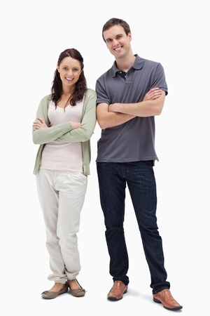 Smiling couple crossing their arms against white background Stock Photo - 13607248