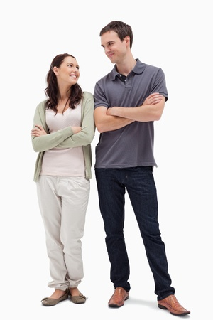 smiling couple looking at each other and crossing their arms against white background photo