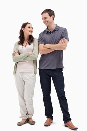 Couple with a complicit smile while crossing their arms against white background photo
