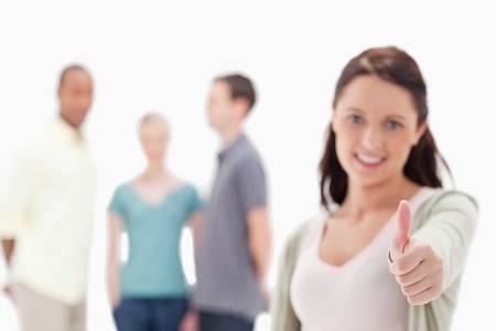 19's: Close-up of a woman with focus on her thumbs-up with friends in background Stock Photo
