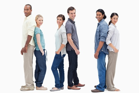 Three couples standing back to back against white background Stock Photo