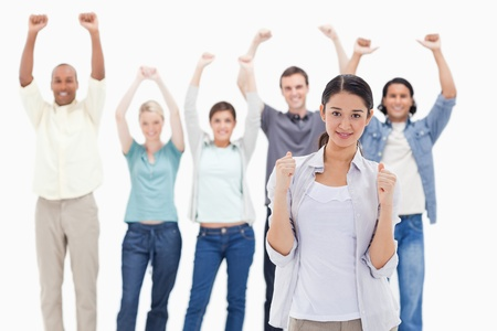 Close-up of a woman clenching her fists with people raising their arms in background photo