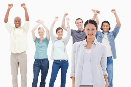 Close-up of a woman with people raising their arms in background Stock Photo - 13606533