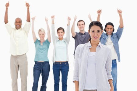 Close-up of a girl with people raising their arms with their thumbs up in background photo