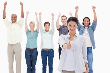 positivismo: Primer plano de una chica con las personas que cr�an a sus brazos y con sus pulgares hacia arriba en el fondo