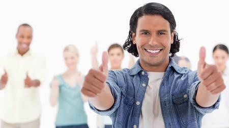 frienship: Close-up of a man with his thumbs-up with people behind against white background Stock Photo
