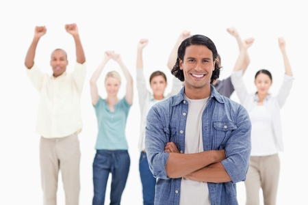 clenching fists: Close-up of a man crossing his arms with people raising their arms in background Stock Photo
