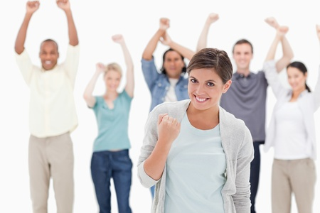 Woman clenching her fist with people behind raising their arms against white background photo