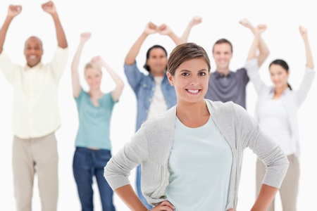 Woman with her hands on hips with people behind raising their arms against white background Stock Photo - 13608599