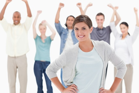 costumers: Woman smiling with her hands on her hips with people behind raising their arms against white background