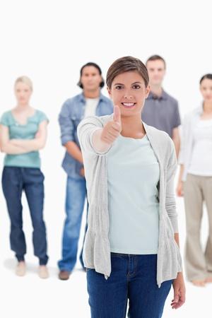 positivism: Primer plano de una mujer que da el pulgar hacia arriba con la gente que est� detr�s contra el fondo blanco