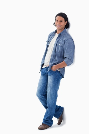 Man smiling while leaning against a wall with white background photo