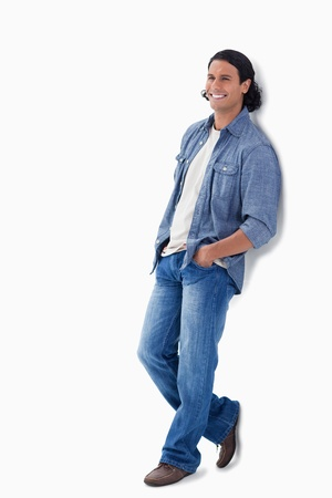 leaning against: Man laughing while leaning against a wall with white background