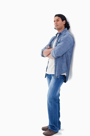 Man raising his eyebrow and leaning against a wall with white background Stock Photo - 13602686