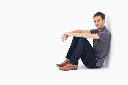 leaning: Man sitting against a wall with white background
