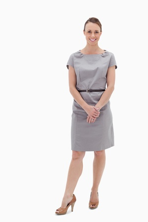 cuerpo entero: Sonriente mujer de pie y sosteniendo sus manos contra el fondo blanco Foto de archivo