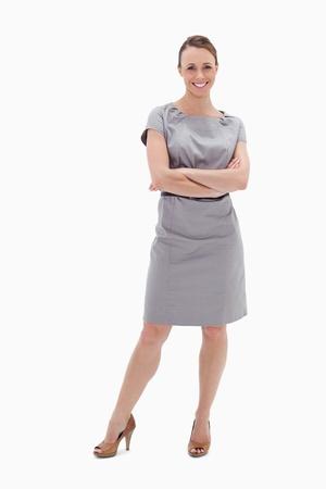 Sourire, femme en robe avec ses bras croisés sur fond blanc Banque d'images