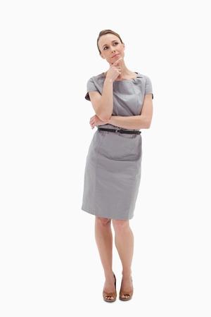 cuerpo entero: Pensativo mujer posando en traje contra el fondo blanco Foto de archivo