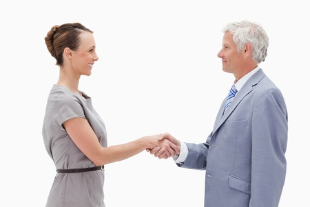 Close-up of a white hair man face to face and shaking hands with a woman against white background photo
