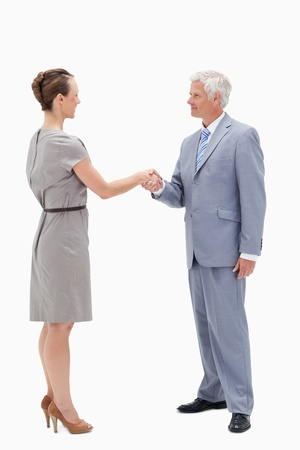 White hair businessman face to face and shaking hands with a woman against white background photo