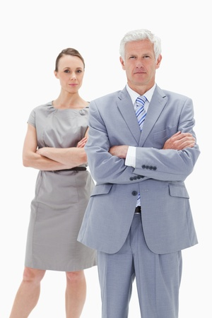 Serious white hair businessman with a woman behind him crossing their arms against white background Stock Photo - 13616007