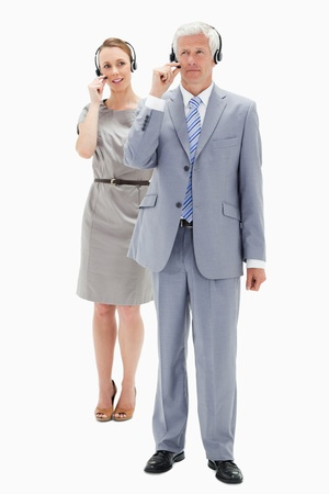 White hair businessman with a woman talking in background while wearing a headset against white background photo