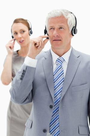 Close-up of a white hair businessman with a woman talking in background while wearing headset against white background photo