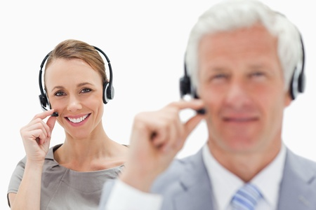 Close-up of a smiling woman talking in background with a white hair man while wearing a headset against white background photo