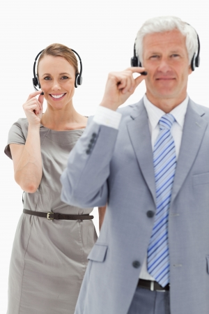 Close-up of a smiling woman in background and wearing a headset with a white hair man against white background photo