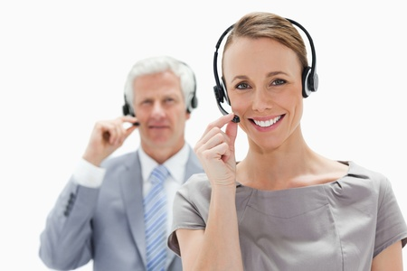 Close-up of a smiling woman wearing a headset with a white hair businessman in background photo