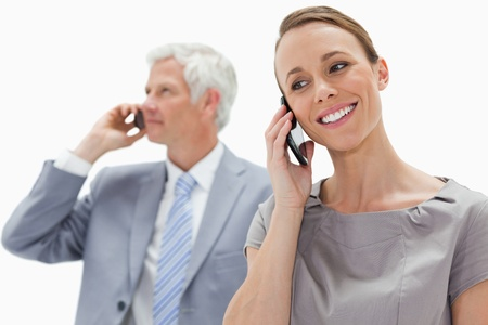 Close-up of a smiling woman making a call with a white hair businessman in background against white background photo