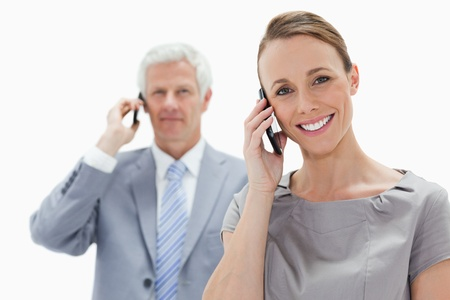 Close-up of a smiling woman making a call with a white hair man in background photo