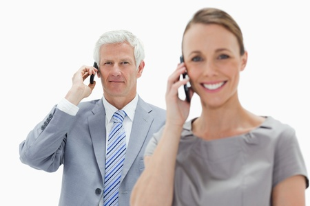 Close-up of a white hair businessman making a call with a smiling woman in foreground against white background photo