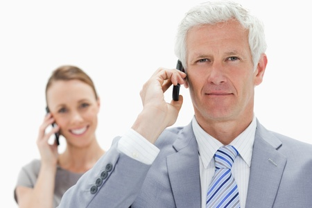 Close-up of a white hair businessman on the phone with a smiling woman in background photo