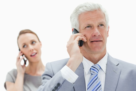 Close-up of a white hair businessman talking on the phone with a woman in background photo