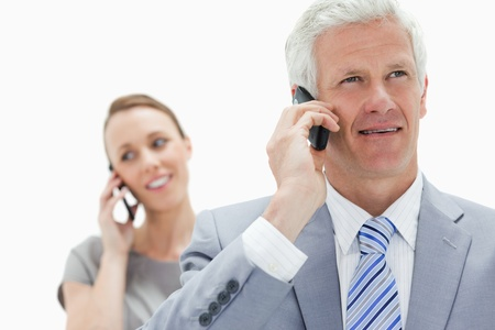 Close-up of a white hair businessman talking on the phone with a smiling woman in background photo