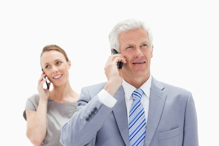 Close-up of a white man hair man dressed in a suit talking on the phone with a smiling woman in background photo