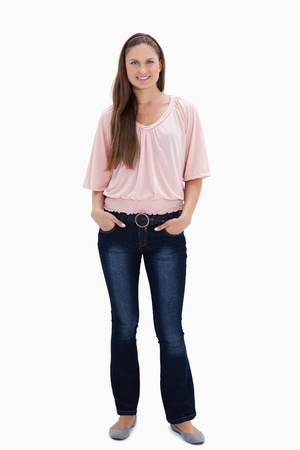 woman full body: Woman smiling with her hands in her pockets against white background Stock Photo
