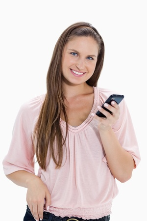 Close-up of a girl holding a mobile phone against white background photo