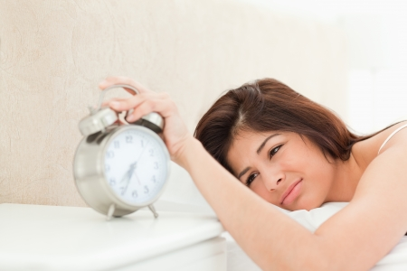 A woman lying on her bed, her hand on the bell of the ringing alarm clock and is also fully awake. photo