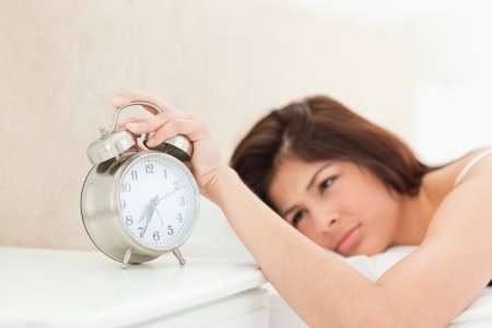 silenced: An alarm clock showing the time is being silenced by an awake woman lying on a bed.