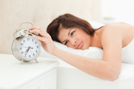 A woman is lying on the bed awake with her hand on the alarm clock, showing the time. photo