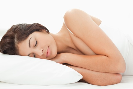 A woman is lying on the bed, with her head resting on the pillow and her arms at her chest and her hands tucked in underneath her head. Stock Photo - 13650647