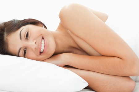 A woman lying on the bed, her head is on the pillow with her eyes open and smiling. Her hands are on the pillow while her arms are on the bed.  Stock Photo - 13651224