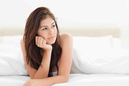A woman with her hand resting against her chin looking to the side and her other arm resting on the bed. photo