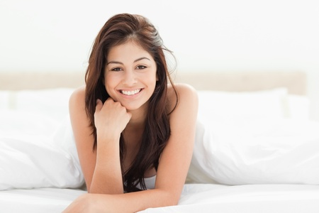 lying forward: A woman lying at the end of the bed looking forward and smiling. Her hand against her chin with her other arm on the bed. Stock Photo