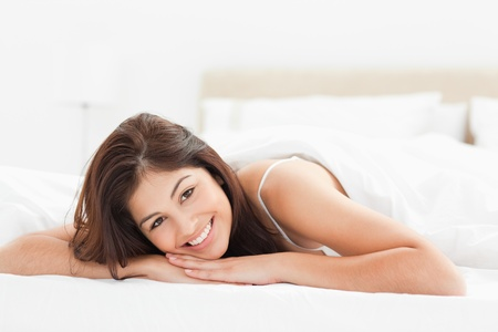 A woman lying at the end of the bed looking forward while smiling and her head resting on both of her hands. photo
